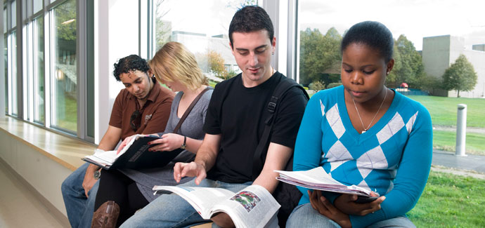 four students with books 450x300px used on academic affairs chelsea campus page