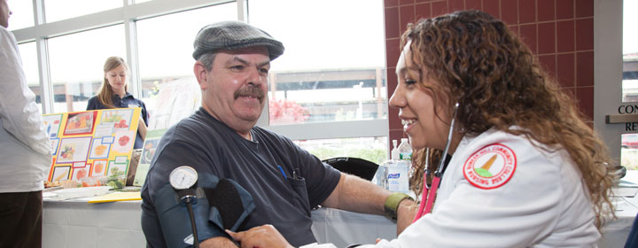 Nursing student measuring patient's blood pressure