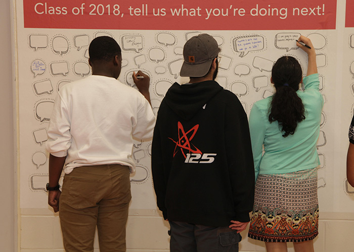 three students writing on a wall