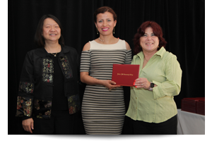 thumbnail of female student receiving diploma from Toni and president eddinger