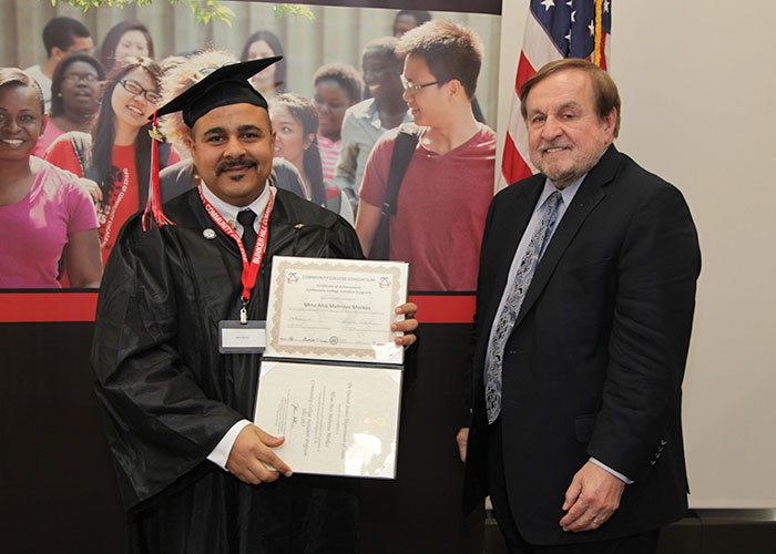 male student posing with certificate and dr. canniff