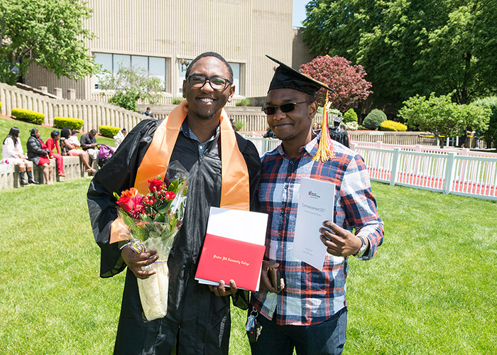 graduate poses with friend and flowers