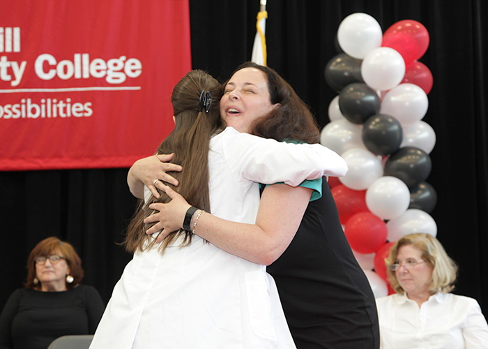 female student and faculty member hugging
