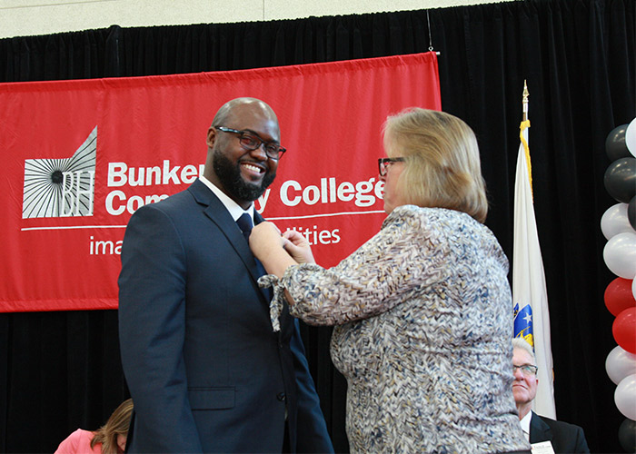 smiling male student receives his nurse pin