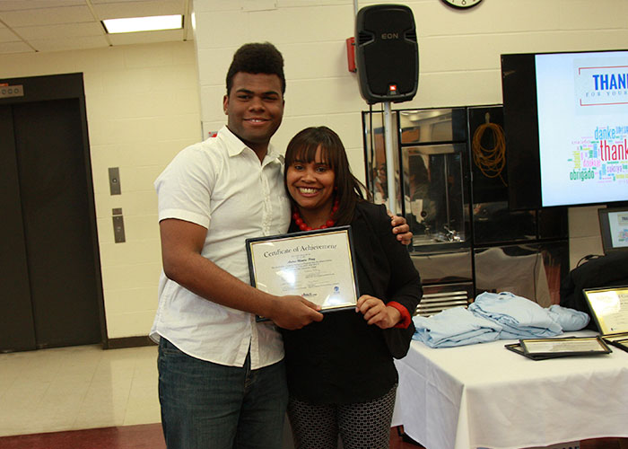 male student posing with certificate with Latoya Robinson