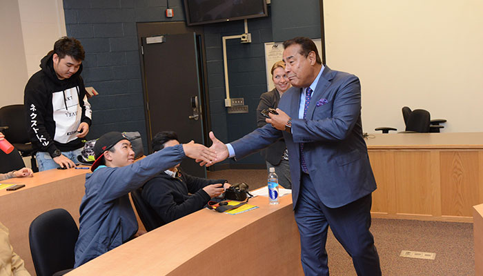 John Quinones shaking hands with a student